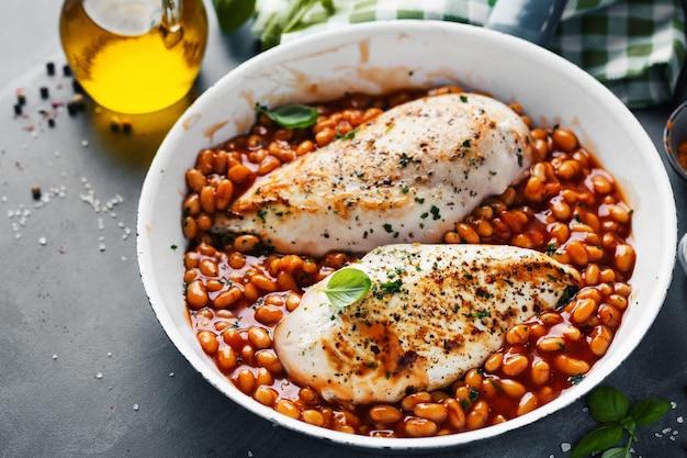 Hähnchenbrust gekocht oder gefüllt mit bohnen in tomatensauce auf pfanne.