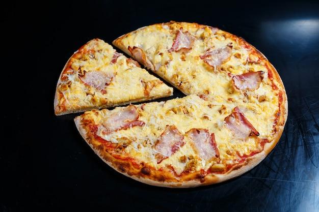 Hähnchenbrust mit cremiger sauce und geriebenem käse auf einer pizza. leckere frische pizza auf dicker kruste mit fleisch