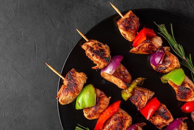 Hähnchenbrustfilet gegrillte grillspieße mit gemüse und rosmarin in einem teller auf schwarzem tisch
