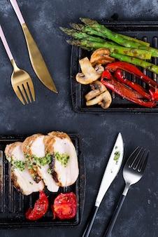 Hähnchenbrustgrill mit grillgemüse und pesto-sauce in einer gusseisernen pfanne