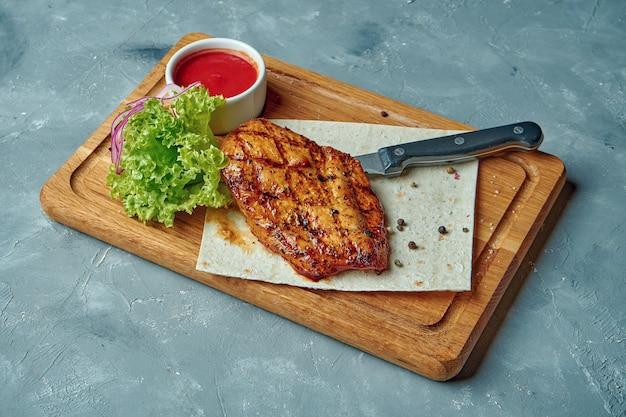 Hähnchenbruststeak in gewürzen auf einem holzbrett auf einem grauen betontisch. gesundes essen