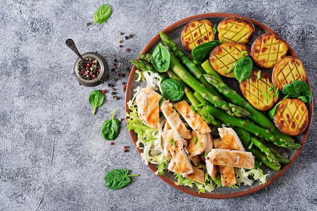 Hähnchenfilet auf einem grill mit einer beilage aus spargel und ofenkartoffeln gekocht. diätmenü. gesundes essen. flach liegen. draufsicht