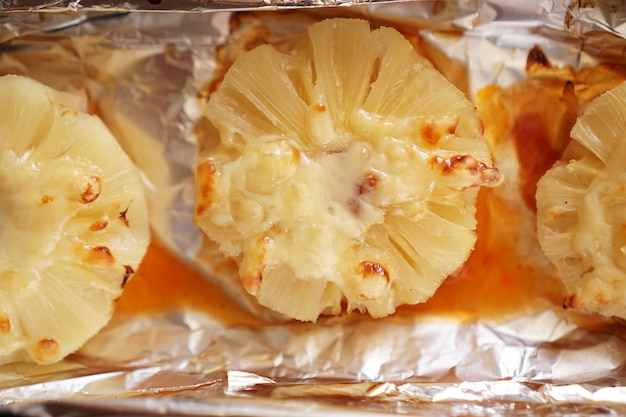 Hähnchenfilet mit ananas auf einem backblech. hähnchen mit ananas im ofen auf folie kochen