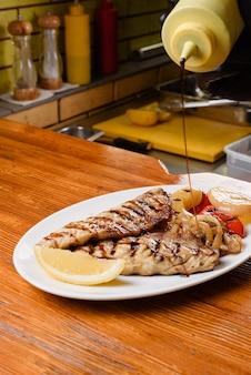 Hähnchenfilet und gegrilltes gemüse mit zitrone auf einem weißen teller auf einem holztisch. sauce auf eine schüssel gießen.