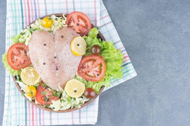 Hähnchenfilets und geschnittenes gemüse auf holzteller.