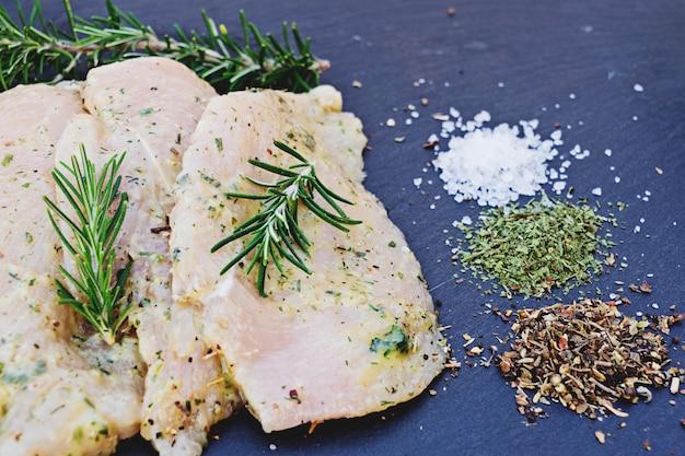 Hähnchenfiletscheiben in sauce und verschiedene gewürze zum kochen, salz, pfeffer und kräuter