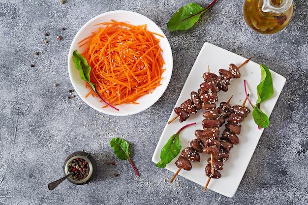 Hähnchenherzen in scharfer soße und möhrensalat. gesundes essen. draufsicht