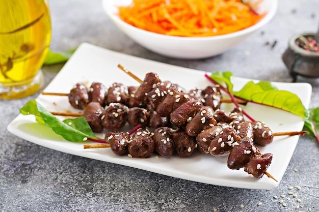 Hähnchenherzen in scharfer soße und möhrensalat. gesundes essen.
