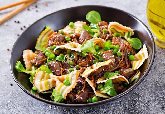 Hähnchenherzen mit karotten in süß-saurer soße mit farfalle-nudeln. gesunder salat