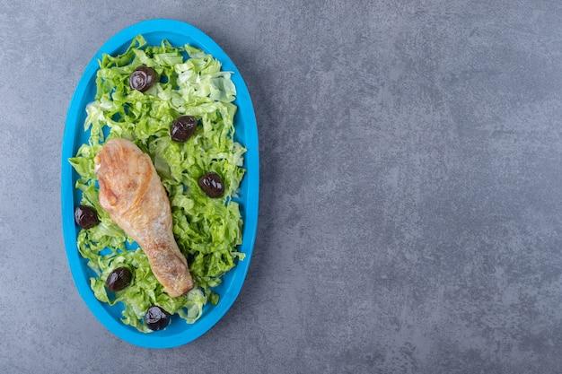 Hähnchenkeule, oliven und salat auf blauem teller.
