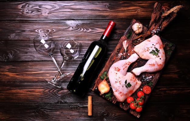 Hähnchenkeulen mit gewürzen und gemüse, dazu eine flasche rotwein.