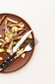 Hähnchenkeulenreste und besteck