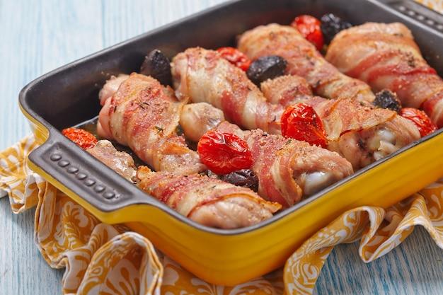 Hähnchenschenkel im speckmantel mit tomaten und oliven