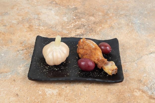 Hähnchenschenkel mit eingelegten kornelkirschenbeeren und knoblauch auf schwarzem teller