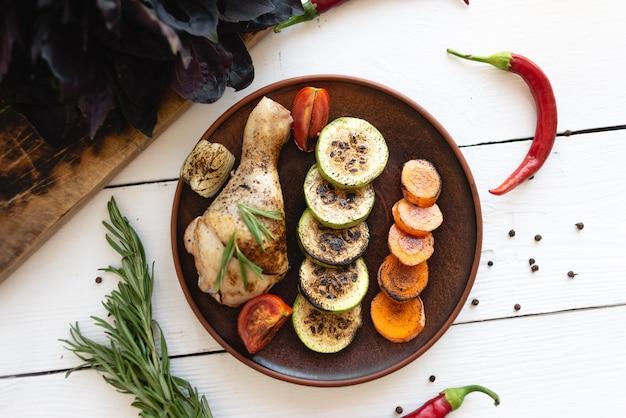 Hähnchenschenkel mit gemüse, ein stück gegrilltes fleisch mit gemüse, ein köstliches restaurantmenü