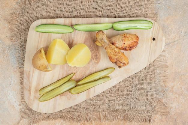 Hähnchenschenkel mit verschiedenem gemüse auf holzbrett