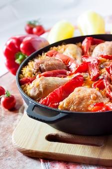Hähnchenschenkel und -beine über einem bett aus reis und rotem paprika in einer gusseisernen eintopfpfanne gebacken