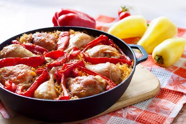 Hähnchenschenkel und -beine über einem bett aus reis und rotem paprika in einer gusseisernen pfanne gebacken