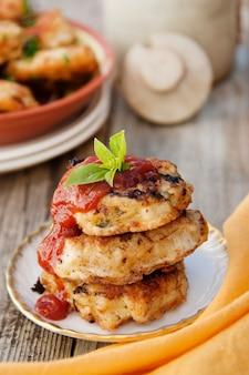 Hähnchenschnitzel mit ketchup. hausgemachtes essen. gesundes essen kochen. rustikales brett. vertikales bild.