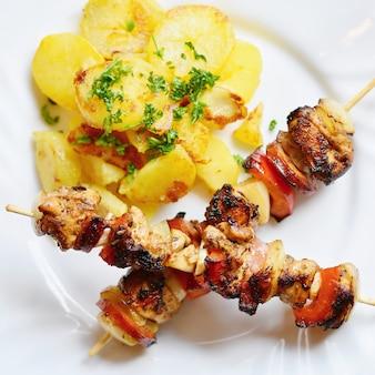 Hähnchenspieß mit kartoffeln und petersilie. ausgezeichnetes fleisch mit gemüse.