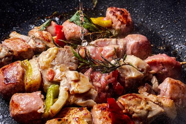 Hähnchenspieße, die in einer steinpfanne gekocht werden und weißwein, der von oben fällt. für den geschmack wird ein rosmarinzweig hinzugefügt.