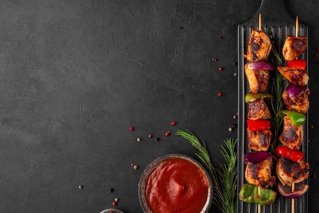 Hähnchenspieße mit paprika- und zwiebelscheiben und rosmarin mit ketchup