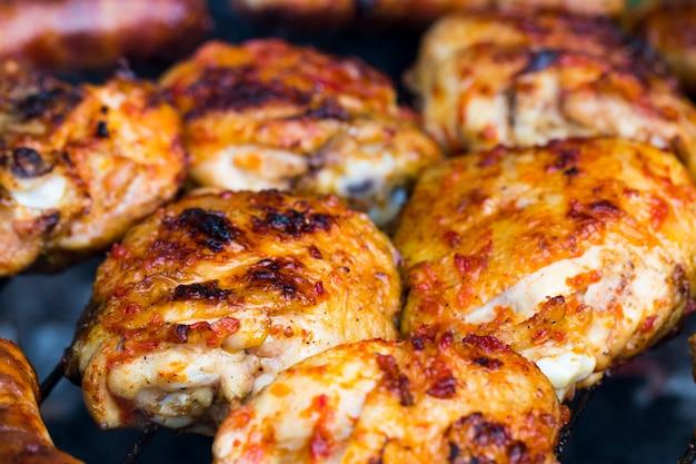 Hähnchenwürste, die auf einem grill im freien gegrillt werden, für den besonderen rauchigen outdoor-geschmack!
