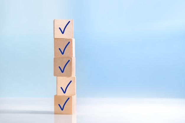 Häkchen auf holzklötzen, blauer hintergrund mit kopienraum. checklistenkonzept