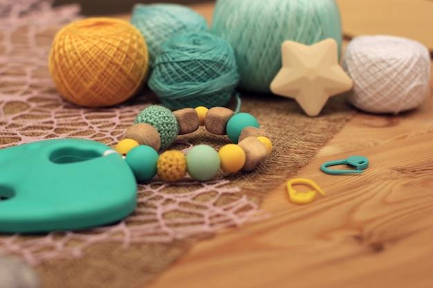 Häkelholz und blaue und gelbe silikonrassel.