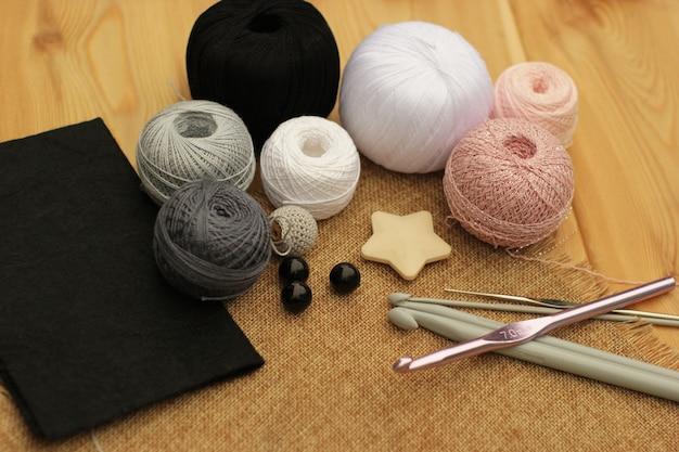 Häkeln sie rosa, graue und schwarze häkelmaterialien. platz kopieren.