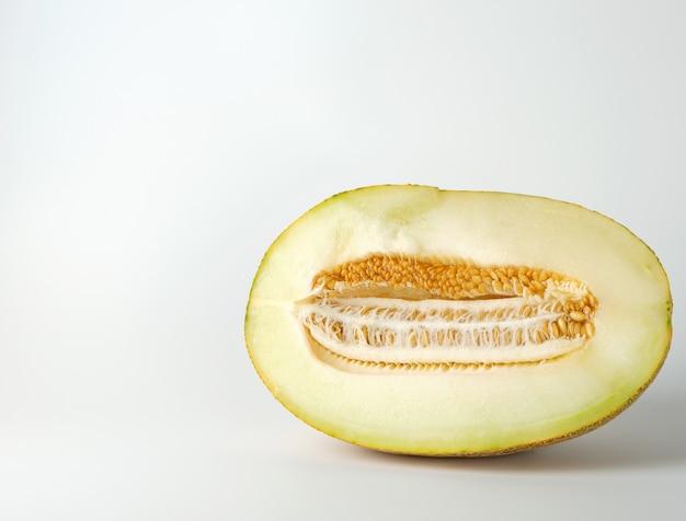Hälfte der reifen gelben melone mit den samen lokalisiert