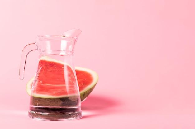 Hälfte geschnittene wassermelone mit krug wasser