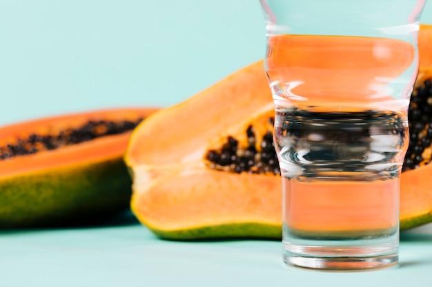 Hälften der papayafrucht und des wassers