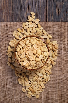Hälften von gerösteten erdnüssen in schüssel und in der nähe auf dunklem holzhintergrund, ansicht von oben