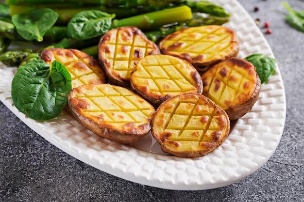 Hälften von ofenkartoffeln und spargel. diätmenü. gesundes essen. vegane küche.