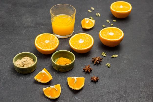 Hälften von orange, sternanis und kardamom auf dem tisch. kurkuma und ingwer in grüner schüssel. ein glas saft. schwarzer hintergrund. ansicht von oben.