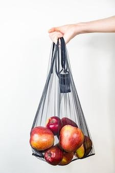 Hält eine wiederverwendbare saitentasche voller äpfel.