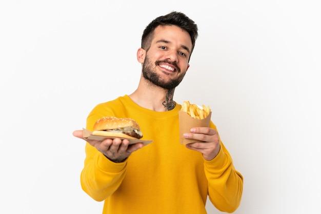 Hält gebratene pommes und cheeseburger über isoliertem hintergrund