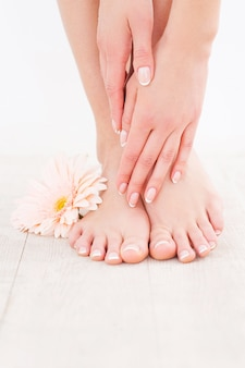 Hält ihre füße sauber und glatt. nahaufnahme einer frau, die ihre füße berührt, während sie auf einem holzboden steht