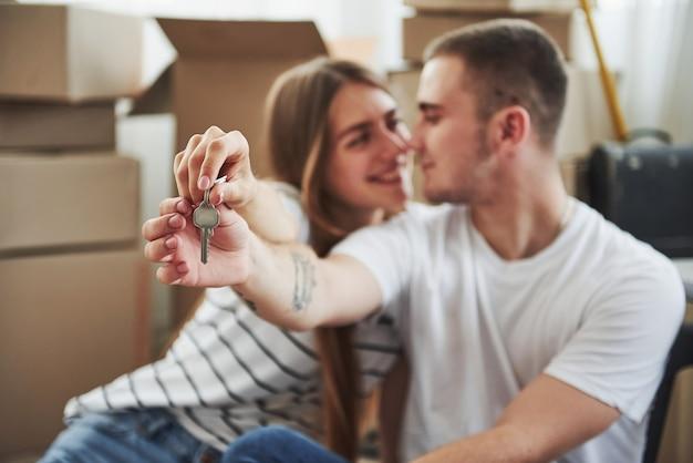 Hält schlüssel ihres neuen hauses. erfolgreiche menschen. fröhliches junges paar in ihrer neuen wohnung. konzeption des umzugs.
