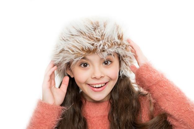 Hält sie im winter warm fröhliches mädchen in pelzmütze isoliert auf weiß kleines kind genießt den winterstil