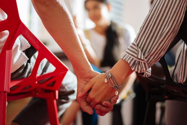 Händchen halten. junge freundliche, zuverlässige menschen, die bei der psychologischen sitzung nahe beieinander sitzen und sich an den händen halten