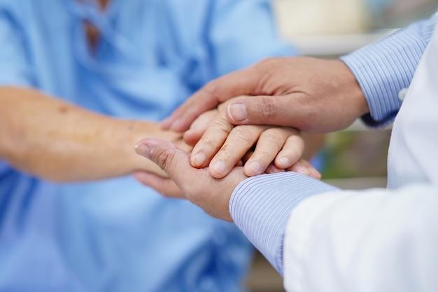 Händchenhalten asiatischer älterer frauenpatient mit liebe.