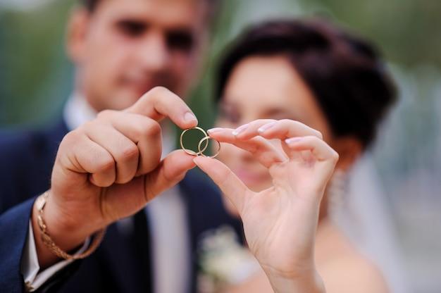 Händchenhalten der braut und des bräutigams in einem ring