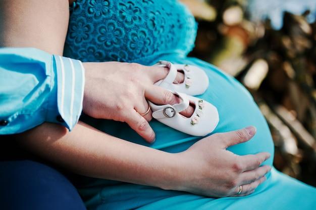 Händchenhalten der schwangeren frau und ihres ehemanns auf bauch mit mädchenbabyschuhen. neues lebensthema