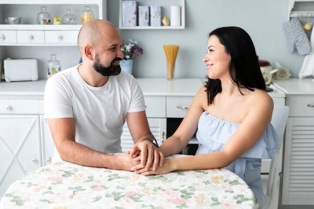 Händchenhalten des ehemanns und der frau auf dem tisch