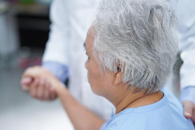 Händchenhaltende asiatische ältere patientin des doktors mit liebe und fürsorge.
