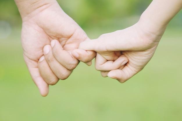 Händchenhaltende frau und mann, glücklicher paarliebhaber im park.