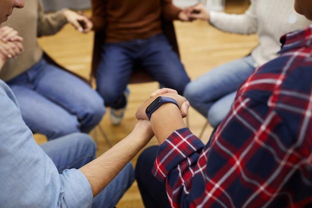 Händchenhaltende personen in der selbsthilfegruppe