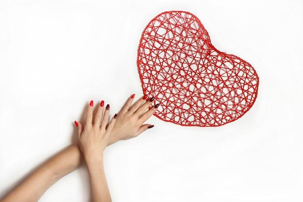 Hände an einem roten herzen auf einem weißen hintergrund. nageldesign auf langen quadratischen nägeln von hellroter zu dunkler farbe des nagellacks.